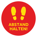 <p>Red with yellow footprints and ABSTAND HALTEN! / (KEEP YOUR DISTANCE in German)</p> Text: ABSTAND HALTEN!