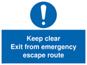 <p>keep clear exit from emergency escape route with exclamation in blue circle</p> Text: keep clear exit from emergency escape route