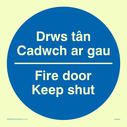 bi-lingual sign - welsh / english in blue circle Text: drws tan cadwch ar gau / fire door keep shut