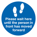 <p>Please wait here until the person in front has moved forward</p> Text: Please wait here until the person in front has moved forward