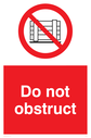 <p>Do not obstruct sign. Red background, with white text. Black gate symbol in a prohibition circle.</p> Text: Do not obstruct