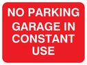 No parking sign, with white text on a red background. Text: No parking garage in constant use