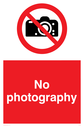 No photography sign, with red background, and white text. Black camera symbol in a prohibition circle. Text: No Photography
