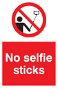 No selfie sticks sign, with red background, and white text. Black selfie stick symbol in a prohibition circle. Text: No selfie sticks