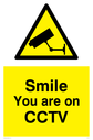 CCTV sign with yellow background, black text and CCTV symbol. Text: Smile you are on CCTV