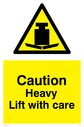 <p>Heavy warning symbol in warning triangle</p> Text: Caution Heavy lift with care