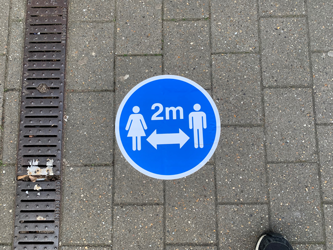 Example image of 2m distance floor graphic applied to external paving for temporary use