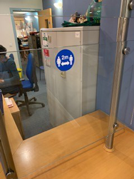 Example image of 2m distance signage in use in a healthcare setting